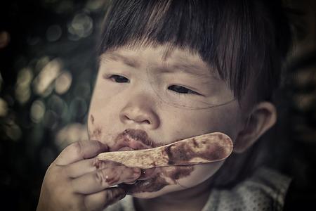niños pobres: los niños pobres que comen el helado Foto de archivo