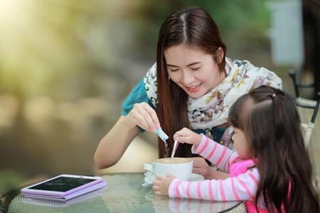 Jonge moeder ontspannen samen met haar kleine kind meisje in de zomer buiten