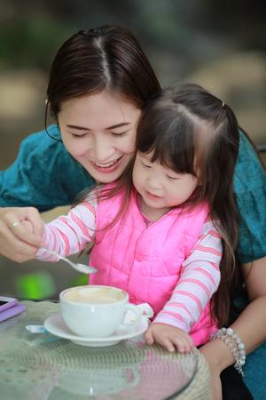 niños desayunando: Madre joven de relax junto a su niña niño en verano al aire libre