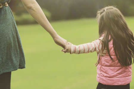child's: Mother holding a hand of her daughter in summer day outdoors