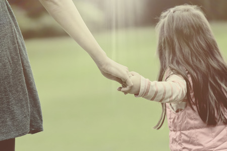 Mother holding a hand of her daughter in summer day outdoors vintage Stock Photo