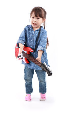 asian baby girl: Little asian girl plays with a toy guitar on a white background