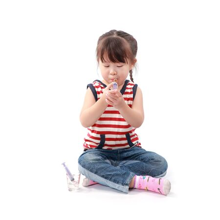 take medicine: little asian girl take a medicine on white background