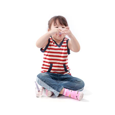 jarabe: Niña asiática tomar un medicamento en el fondo blanco