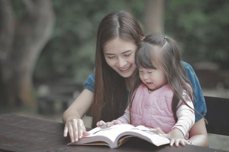 kid book: young mother reading a book to her cute daughter vintage style