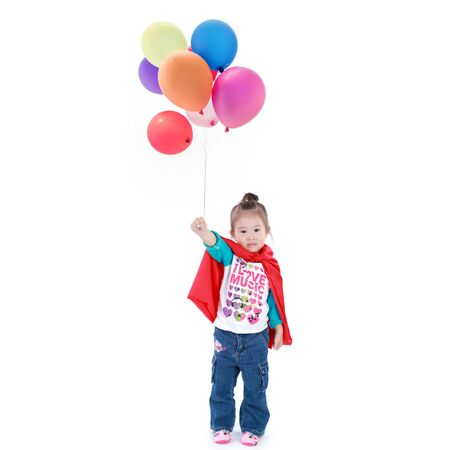 Superhero little asian girl in a red raincoat with balloons on white background