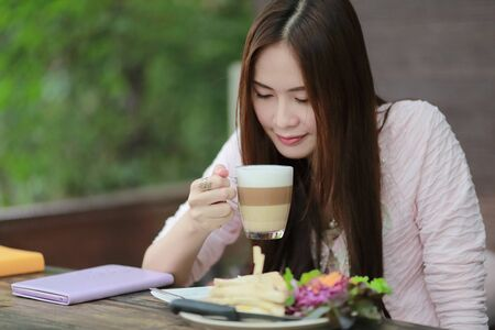 gril: Beautiful asian gril drinking coffee in cafe restaurant
