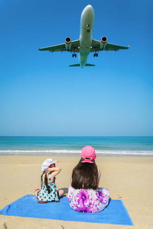 Happy child playing at the beach in summer with airplane photo