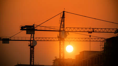steel structure: Silhouette of tower crane on a construction site at sunset