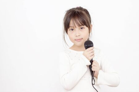 Pretty little asian girl with the microphone in her hand High key color on white background photo
