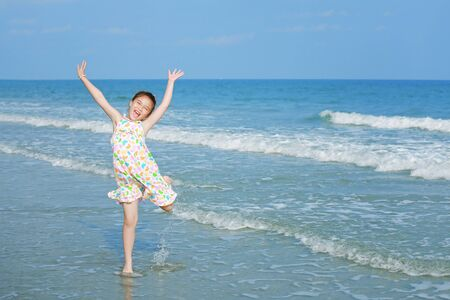 Happy little girl on the beach photo