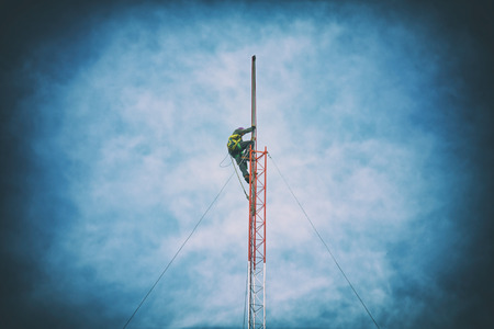 communication industry: Repairman working on communications tower retro style Stock Photo