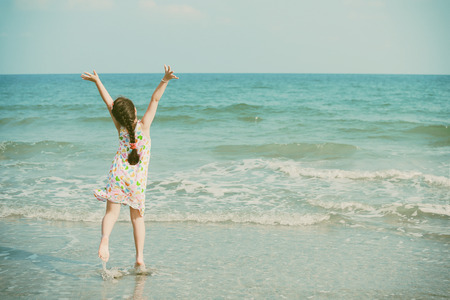 Happy little girl on the beach retro style photo