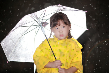 Cute little girl with a umbrella in the rain