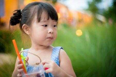 Asian little girl drinking juice Standard-Bild