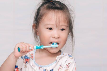 Une fille se brosse les dents