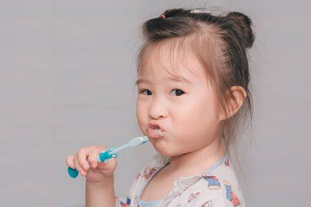 A girl brushing his teeth