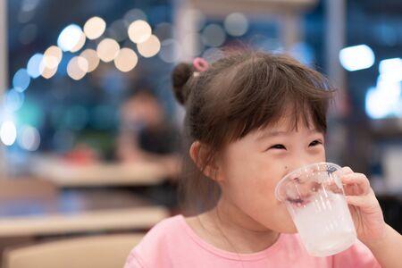 Little asian girl drinking water Standard-Bild