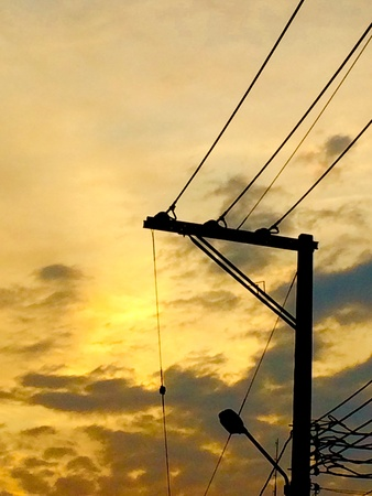 colour: Silhouette of electrici pole with sunset