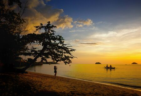 amazing landscape of sea and tropical beach in Thailand at sunset time for vacation(selective focus at oarsman and boat) Imagens