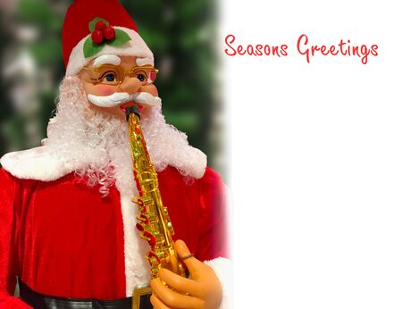 Santa Claus toy blowing the jazz  at Christmas time with copyspace for your text,wallpaper,card,greeting Stock fotó