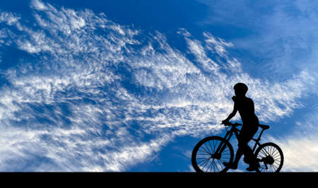 Silhouette of young man riding on modern bike on the road with bright cloud sky background, Sport and active life concept in the summer ,
