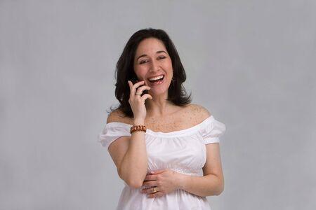 humoristic: Una hermosa latina dama vestida de blanco riendo en un tel�fono celular, aislados en blanco  Foto de archivo