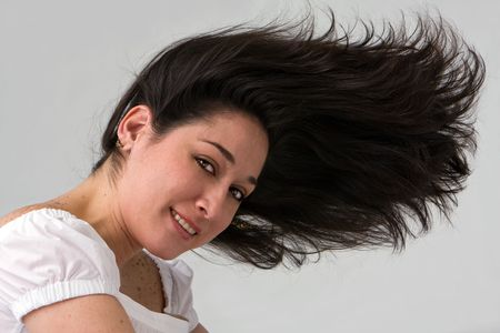 A beautiful latina lady with wild hair blowing to the front, isolated on white Stock Photo - 3129668