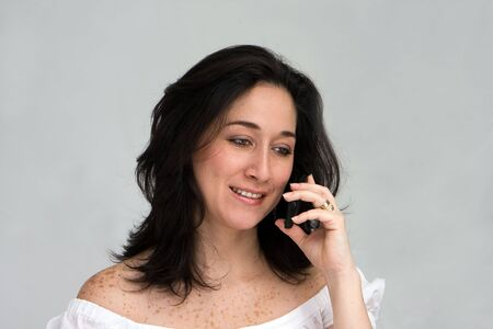 A beautiful latina lady calling on a cell phone, isolated on white Stock Photo - 3129643