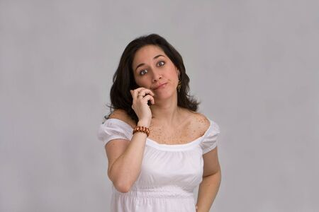 duh: A beautiful latina lady dressed in white having a conversation on a cell phone