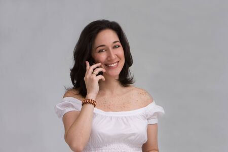 A beautiful latina lady dressed in white smiling on a cell phone, isolated on white Stock Photo - 3129626