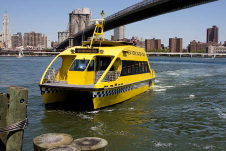 water transportation: New York Citys water taxi arriving at Fulton Ferry landing in Brooklyn. Here seen with the Brooklyn Bridge in the background on a bright sunny day with a depp blue sky.