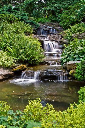 feng shui: Beautiful multi-layered waterfall between vegetation.