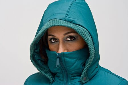 A young woman wearing a green winter coat using the hood to cover her head so that only her eyes are visible, isolated on white
