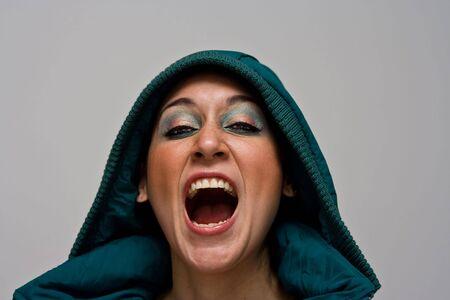 aggressively: Una bellissima giovane donna urlando aggressivo che indossa un mantello verde inverno e la cappa sopra la testa, isolata su bianco