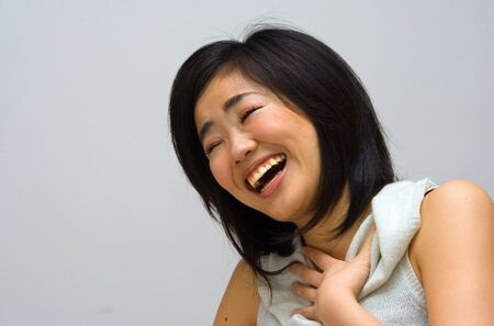 collared shirt: Beautifull Oriental woman in a white collared shirt laughing