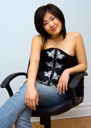 far eastern: Beautiful Oriental woman sitting comfortable in a chair