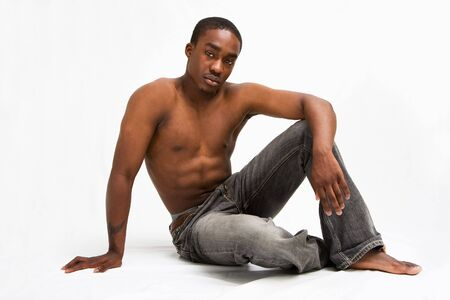 A handsome topless dark skinned man sitting relaxed, isolated on white Stock Photo - 3147932