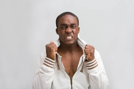 Dark skinned handsome young man, grabs his stylish white hooded shirt; Very angry! Isolated