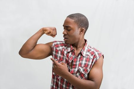Young dark skinned handsome guy proudly pointing at his biceps showing how strong he is wearing a checkered shirt, isaolated photo