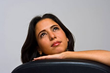 so�ando: Una bella chica joven hispano d�as so�ando, buscando con sus ojos brillantes y el apoyo a su cabeza con la mano, aislados en blanco Foto de archivo