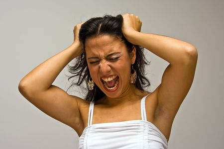 A young beautiful latina woman screeming of frustration and pulling her hair with both hands wearing a white shirt, isolated on white