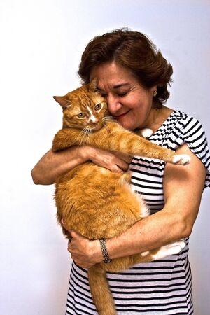 gato naranja: Una se�ora de edad avanzada en un blanco y negro a rayas celebrar una camiseta naranja cat.  Foto de archivo