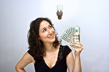 Woman waving money and looking up. Having an environmentally friendly idea with an energy saving fluorescent light bulb floating above her head, on a white background