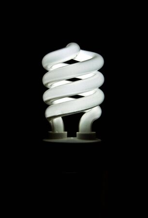 A glowing fluorescend light bulb that is environmently friendly and saves . Stock Photo