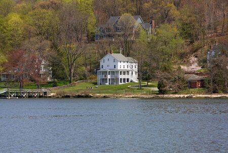 A remotely located white Victorian mansion on the water and in the woods on a spring day. photo