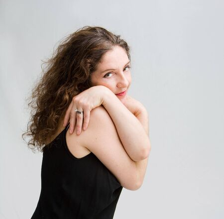 Beautiful tender middle aged woman dressed in black hugging herself, isolated