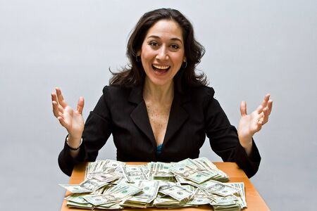 Happy business woman sitting at a table covered with stacks of money isolated on a white background Imagens