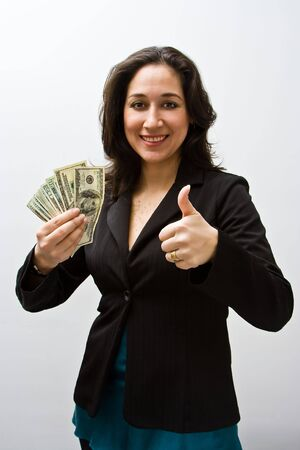Smiling business woman holding up fanned money and a thumb up, isolated on white Stock Photo - 3292047