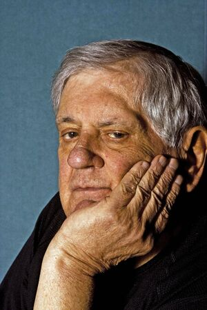 Dramatic side portrait of a senior man with his hand on the side of his face wearing a black shirt isolated on grayblue photo